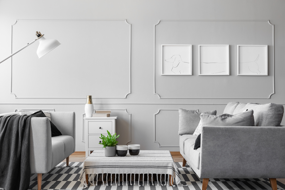Posters on the empty grey wall of simple living room with two sofas, coffee table and white lamp, real photo