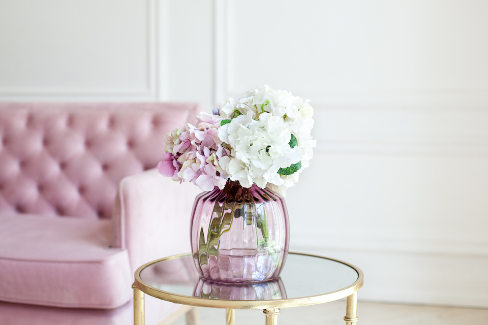 Bouquet of pastel hydrangeas in glass vase.