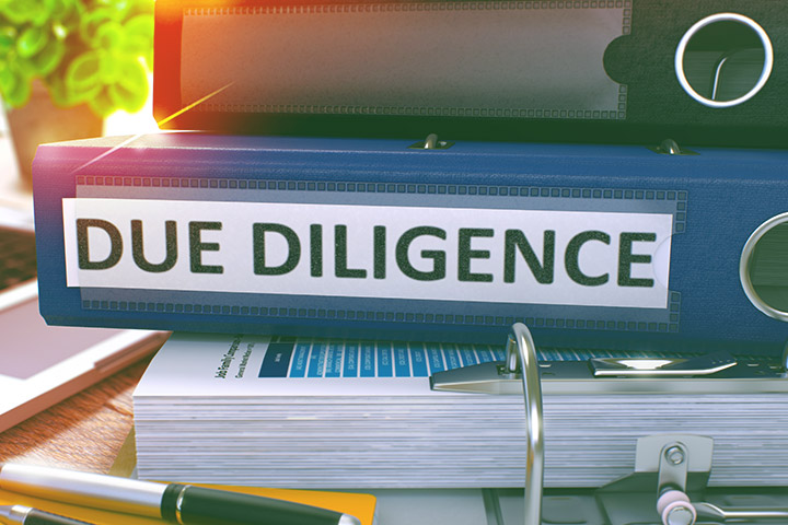 """Binders in a pile with a large blue binder in the middle labeled """"Due Diligence."""""""