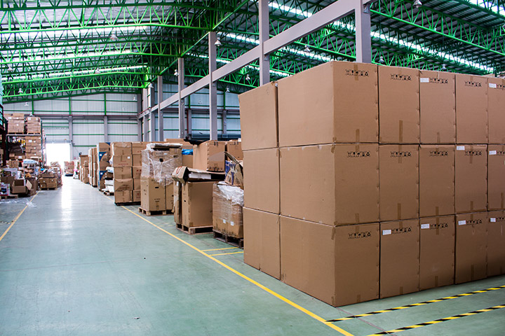A warehouse with piles of boxed stacked three high throughout the warehouse.