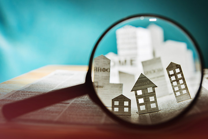 A graphic of a magnifying glass magnifying a small city made out of white paper.