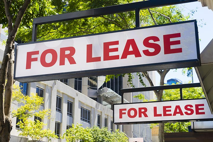 """""""For Lease"""" signs along a city street in front of a large building."""