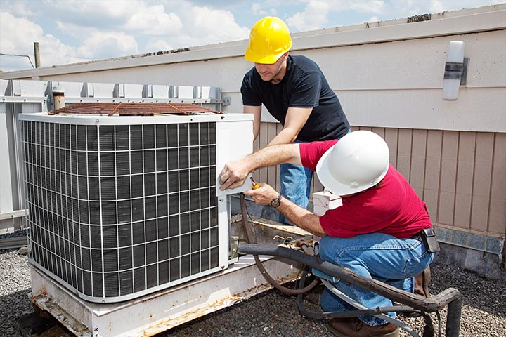 Two maintenance workers fixing an outdoor air conditioning unit.