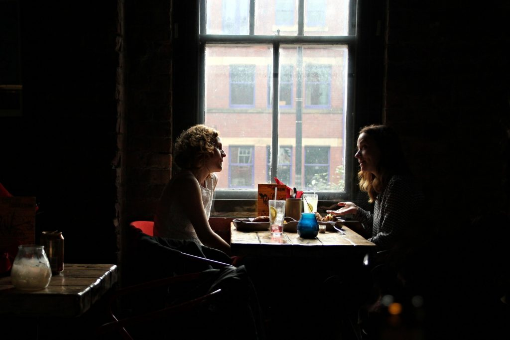 Two women sitting at a table in a dark cafe chatting and enjoying drinks.
