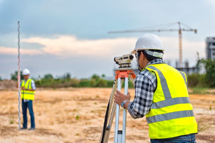 Two construction workers using a device to measure the distance between two points on a construction site.
