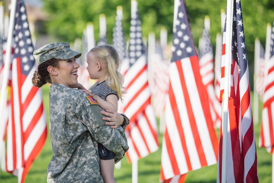 American female soldier in uniform in a field of flags with a little blonde girl.