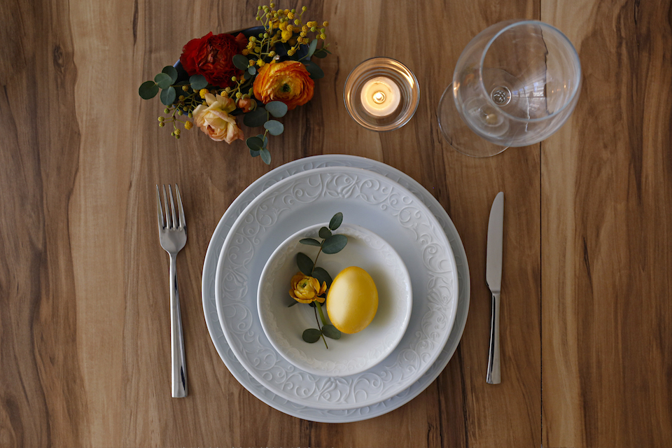 Easter table setting composition with traditional golden painted egg, beautiful tableware on natural dark wood textured table. Top view, copy space, close up, background.