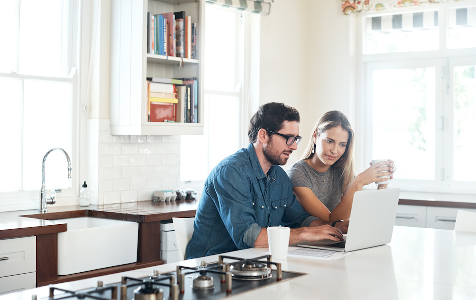 Shot of a young couple using a laptop together at home